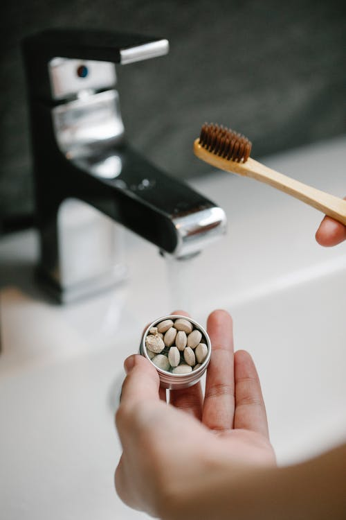 Hand of anonymous female with wooden toothbrush and toothpaste tablets standing near washbasin in bathroom during daily hygiene routine in morning