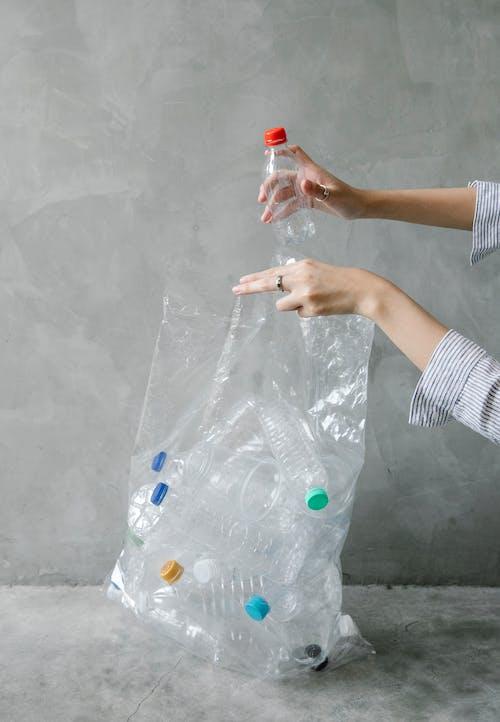 Crop woman putting plastic bottle into bag
