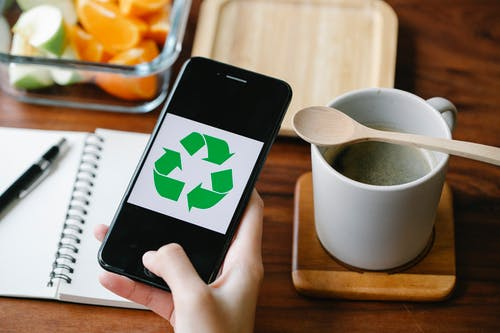 Crop person using recycling app on smartphone against coffee