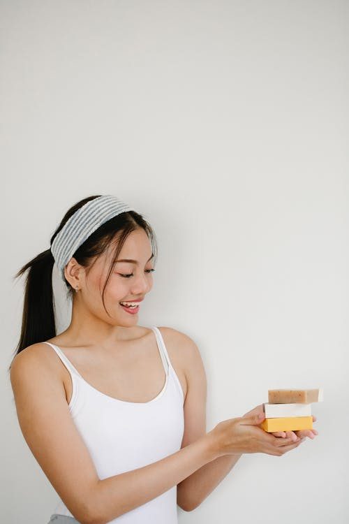 Smiling young ethnic female in headband with pile of ecological soap blocks on light background