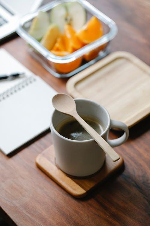 Organic spoon on mug of coffee on coaster