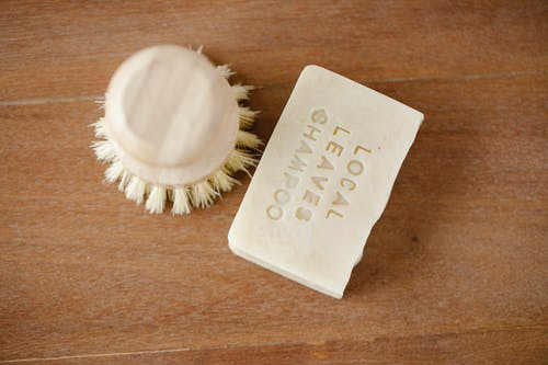 Top view of zero waste beauty brush and dry shampoo with inscription on brown background