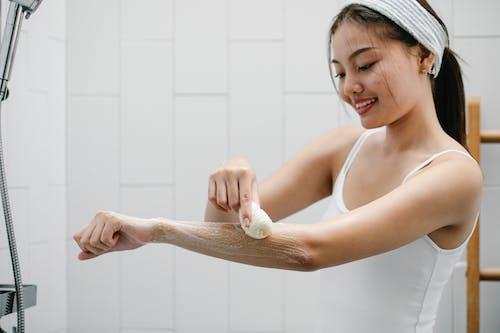 Positive Asian woman washing arm