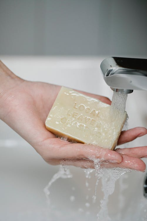 Crop person washing hand with soap