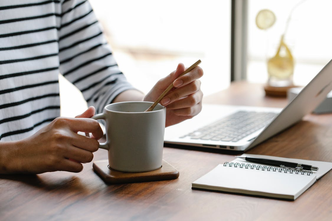 Crop unrecognizable freelancer in casual clothes sitting at table with white cup of hot drink near laptop and notebook