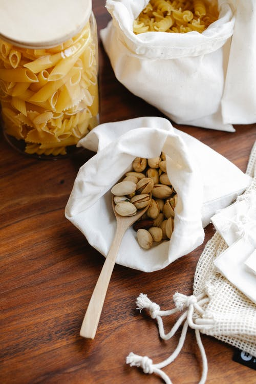From above pistachios in white recycling bag with wooden spoon and pasta near penne in glass jar and rotini in white recycling bag on wooden table