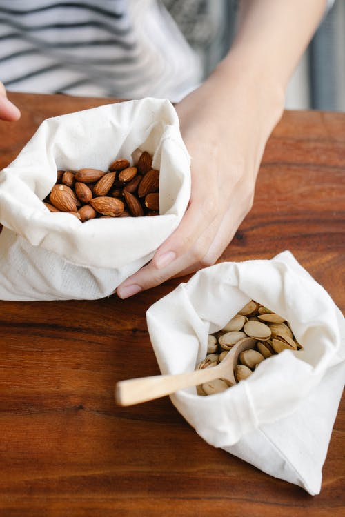Crop person showing almonds in white bag near pack of pistachios with wooden spoon on table