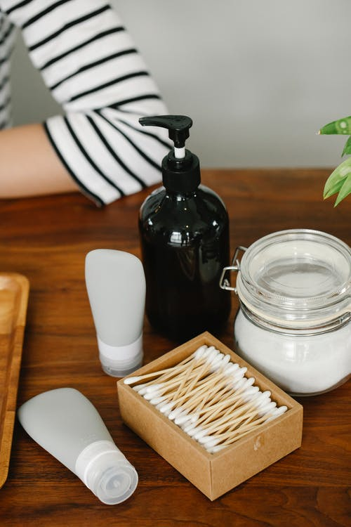 Anonymous person sitting near white plastic tubes of skincare cosmetics lotion dispenser glass jar of white cream and ear sticks in box on table