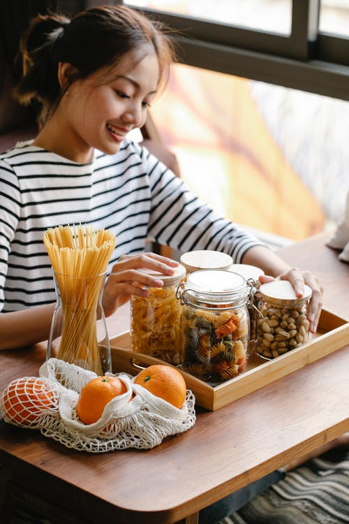 Smiling Asian woman sitting at table near oranges and pasta
