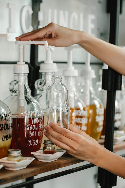 Crop unrecognizable person pouring red soap into plastic bottle while pressing large dispenser near white saucers and glass jars on shelf