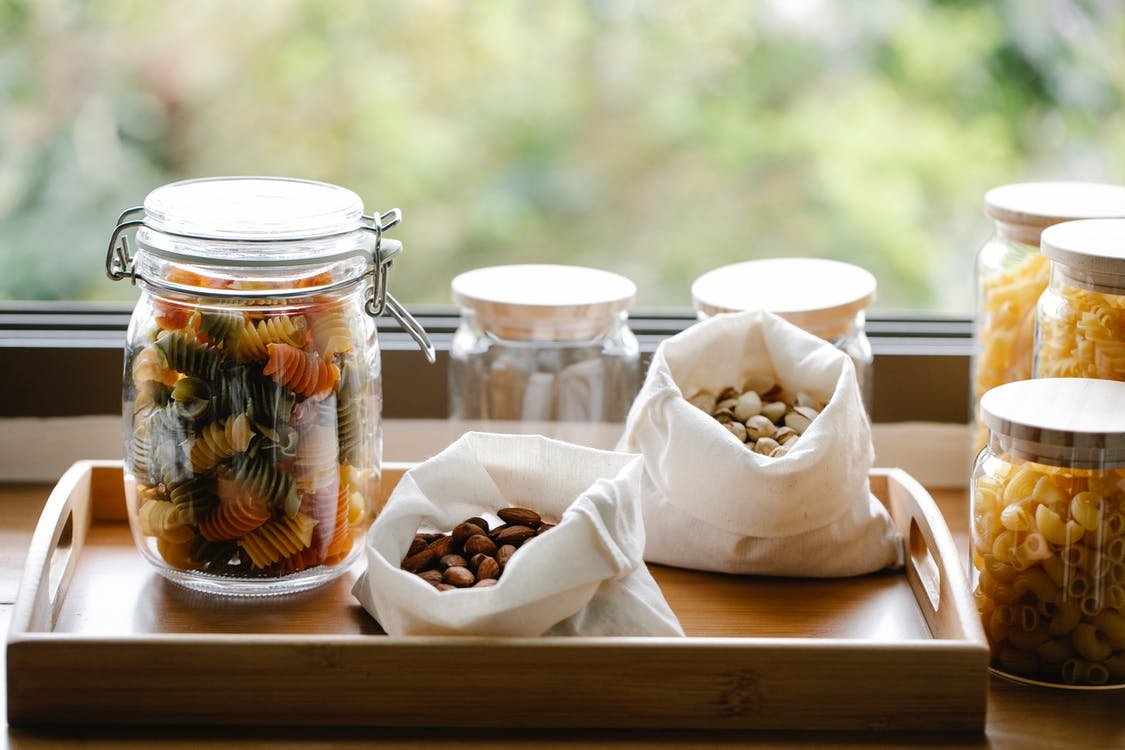 Glass jar with rotini pasta placed on wooden tray near ECO friendly bags with almonds and pistachios in light room near window on blurred background