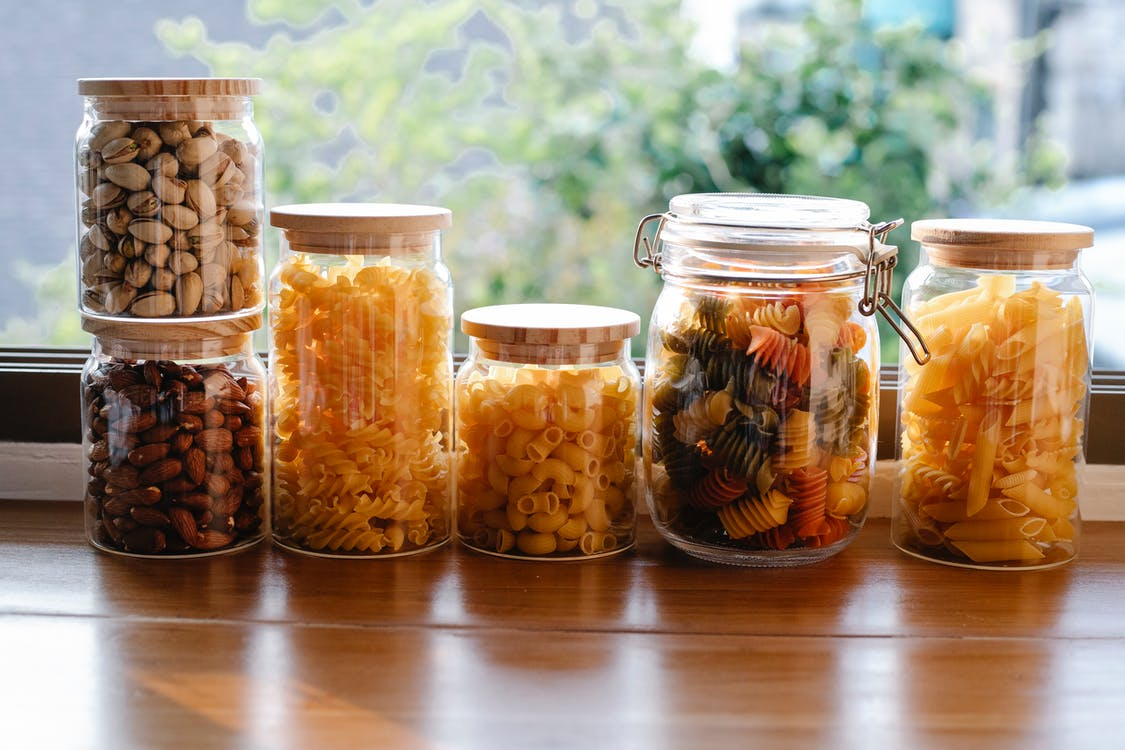 Glass jars filled with assorted types of uncooked pasta and pistachios with almonds placed on wooden table near window in light room