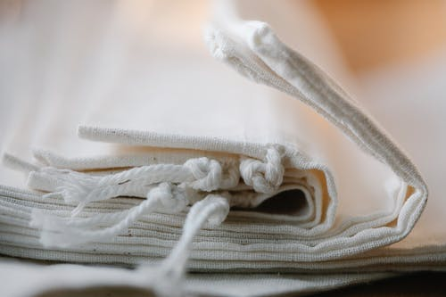 Pile of folded white cotton bags with ropes made of ecological cloth placed on table in light room on blurred background