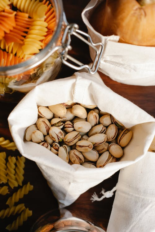 Top view of ECO friendly sack full of pistachios placed on table near raw pasta and ripe pumpkin in light room
