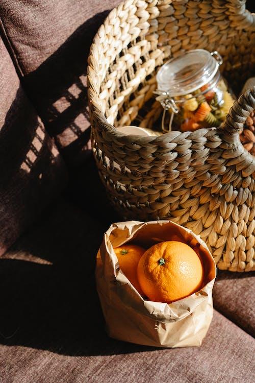 Heap of oranges near basket