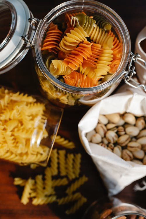Top view of glass jars with uncooked fusilli and rotini pasta placed on table near ECO friendly bag with pistachios
