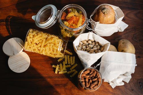 Top view jars of raw pasta placed on wooden table near ECO friendly sacks with pistachios and almonds near pumpkin and potatoes