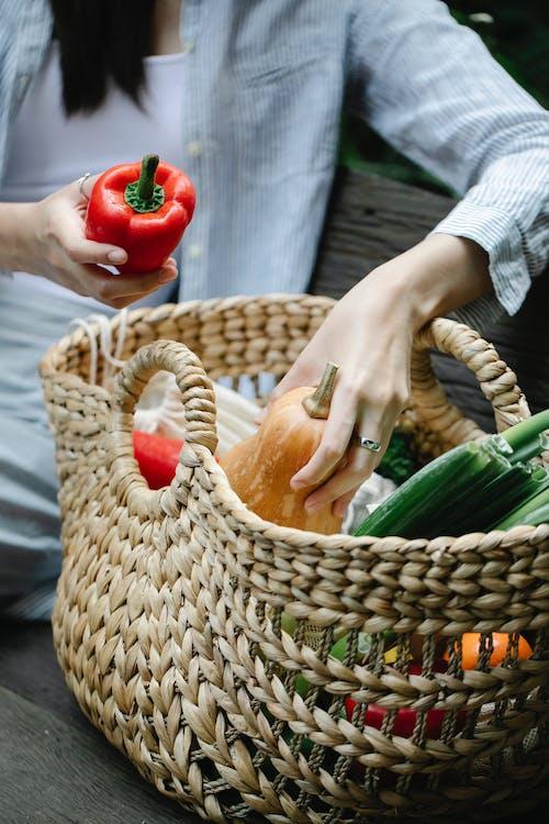 Crop woman putting vegetables into wicker basket