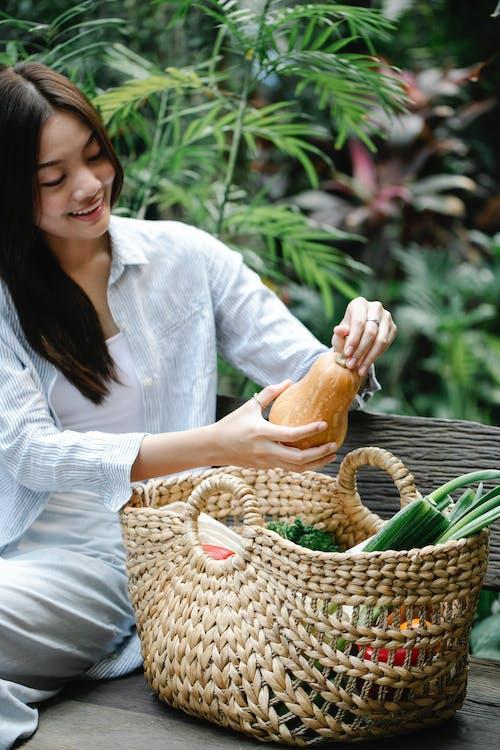 Crop cheerful Asian woman placing ripe vegetables in basket