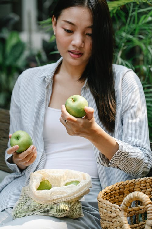 Crop Asian woman with green apples in lush garden