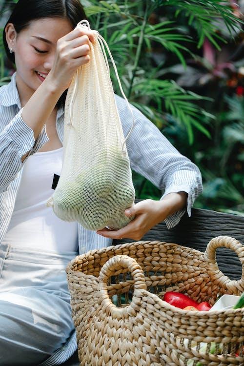 Crop smiling Asian woman placing apples in basket in garden