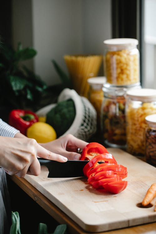 Faceless woman chopping bell pepper during lunch preparation in kitchen