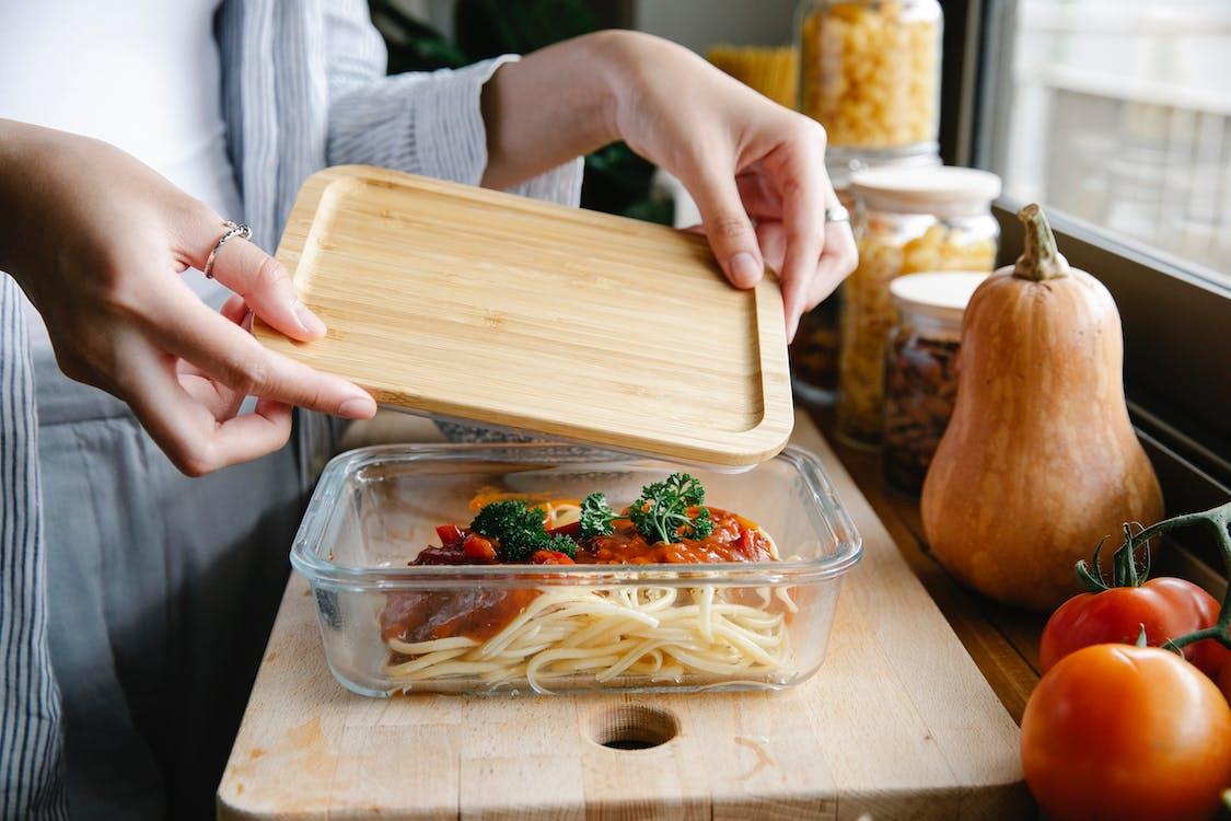 Unrecognizable woman preparing delicious homemade pasta with tomato sauce in kitchen