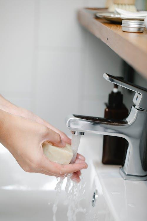 Crop person washing hands in bathroom