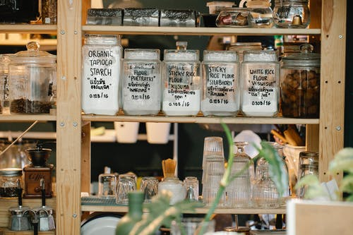 Glass jars with dry food and glassware on shelf