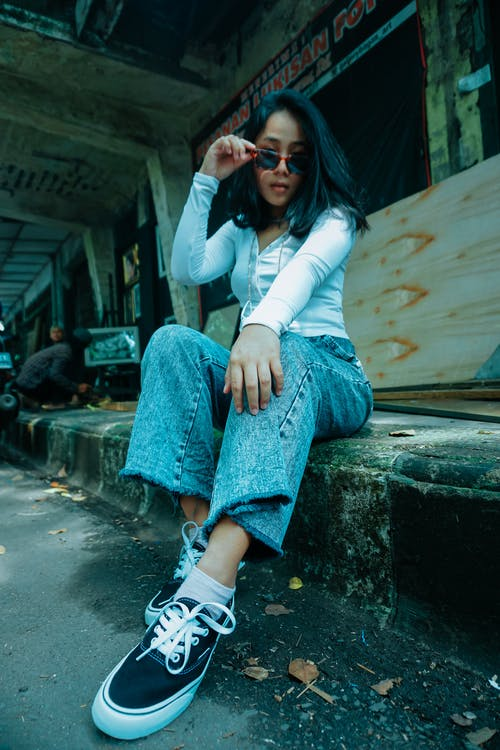 From below of Asian female in casual outfit and sunglasses sitting in abandoned underground carriage and looking at camera