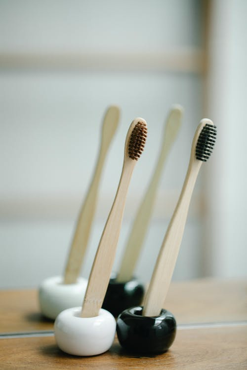 Set of bamboo toothbrushes near mirror