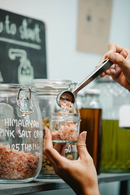 Crop anonymous tester putting spice from big transparent container into glass jar in supermarket