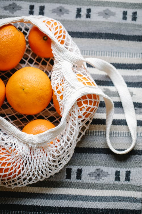 Top view of ripe many tangerines places on striped gray textile with ornament