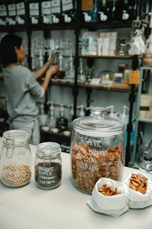 Crop anonymous female near shelves and table with glass jars filled with organic food