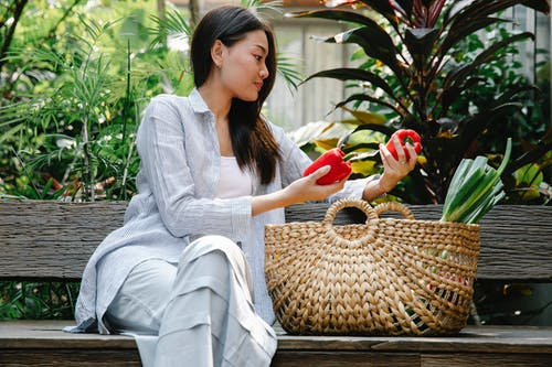 Calm Asian female in casual clothes sitting on wooden bench among green plants and putting ripe red peppers in wicker basket in daytime