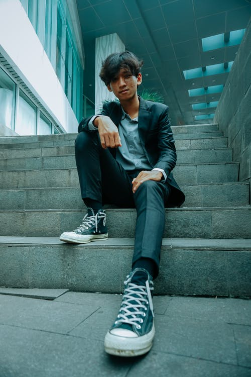 Full body of self assured young Asian male millennial in trendy clothes and sneakers sitting on steps of modern building and looking at camera