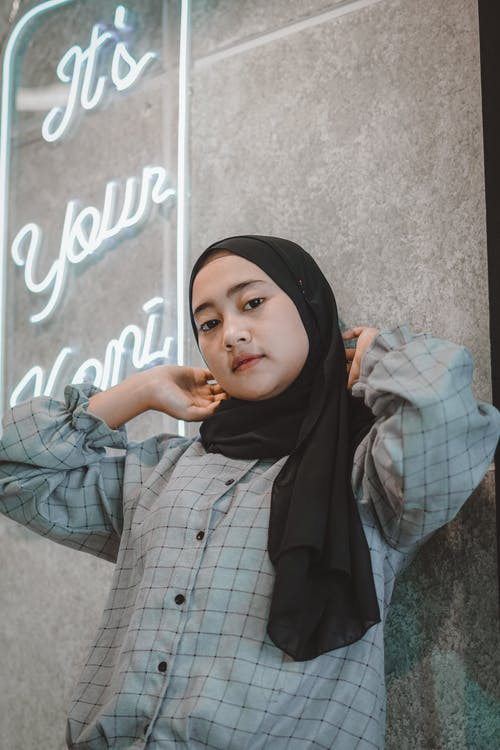 Low angle of serious young Asian lady leaning on wall with neon inscription and looking at camera while adjusting traditional Muslim headscarf