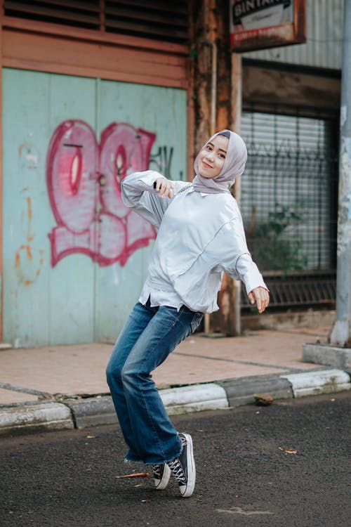 Side view of positive Asian female teenager in casual clothes and traditional hijab standing on tiptoes on street and looking at camera