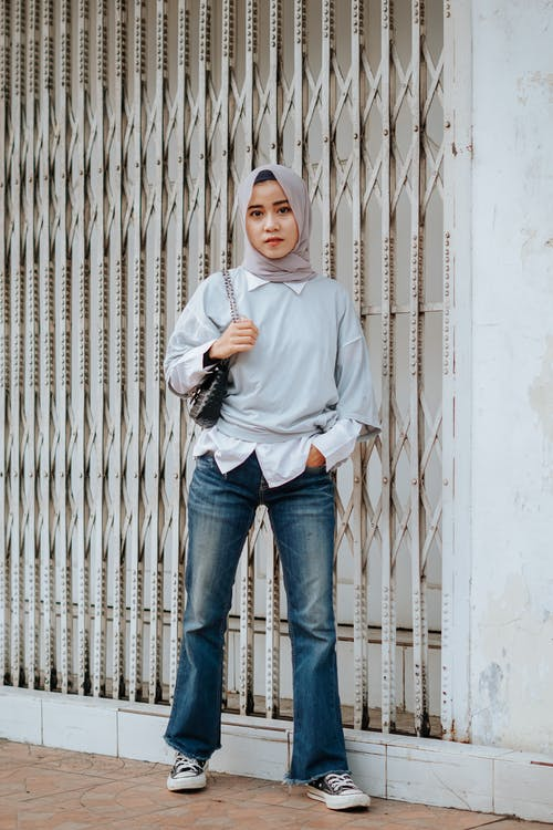 Full body of confident young Muslim lady in stylish outfit and traditional headscarf standing on city street with hand in pocket