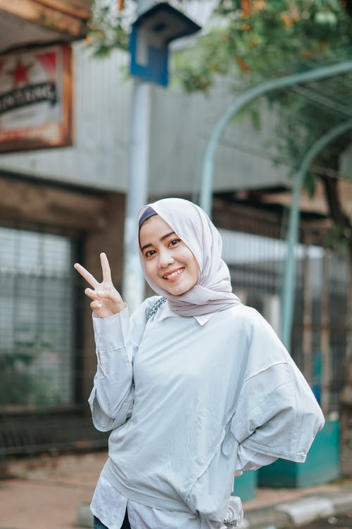 Content young Muslim lady showing V sign and smiling on street