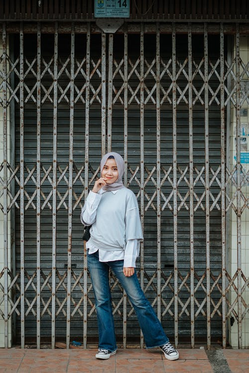 Full length of stylish Muslim female teenager in trendy outfit and traditional headscarf standing on street near old building with shabby metal fence and looking at camera