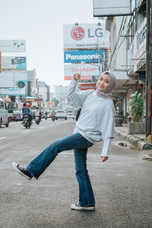 Full body of young Muslim ethnic female smiling and looking at camera near road with cars and motorcycles