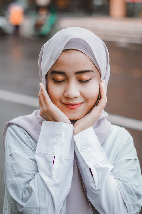 Happy Asian Muslim woman with eyes closed touching chin