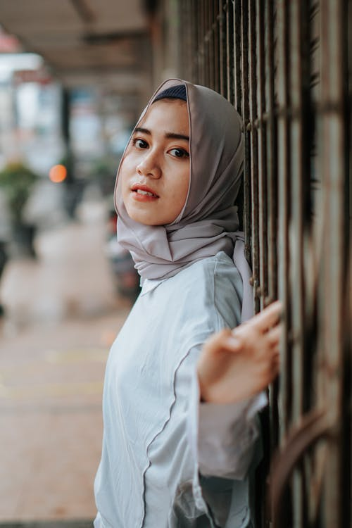 Side view of calm ethnic Muslim female in hijab looking at camera on blurred background of street in city