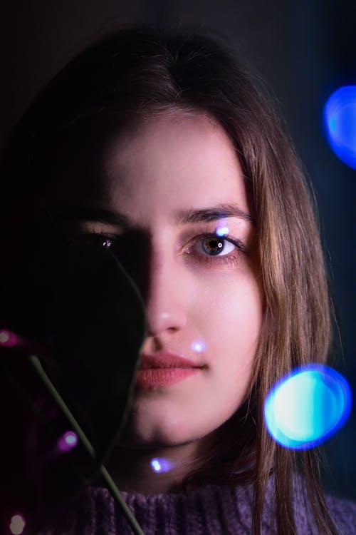 Young gentle female with deep gaze and shadow on half of face looking at camera