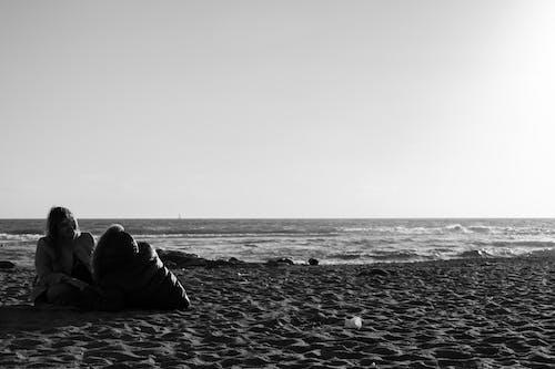 Women sitting on beach near sea