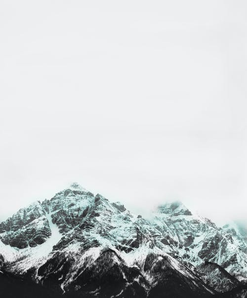 Scenery of rough snowy mountain ridges covered with snow under gloomy sky in winter day