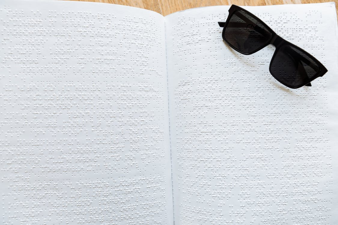 Black Framed Sunglasses on White Braille Paper
