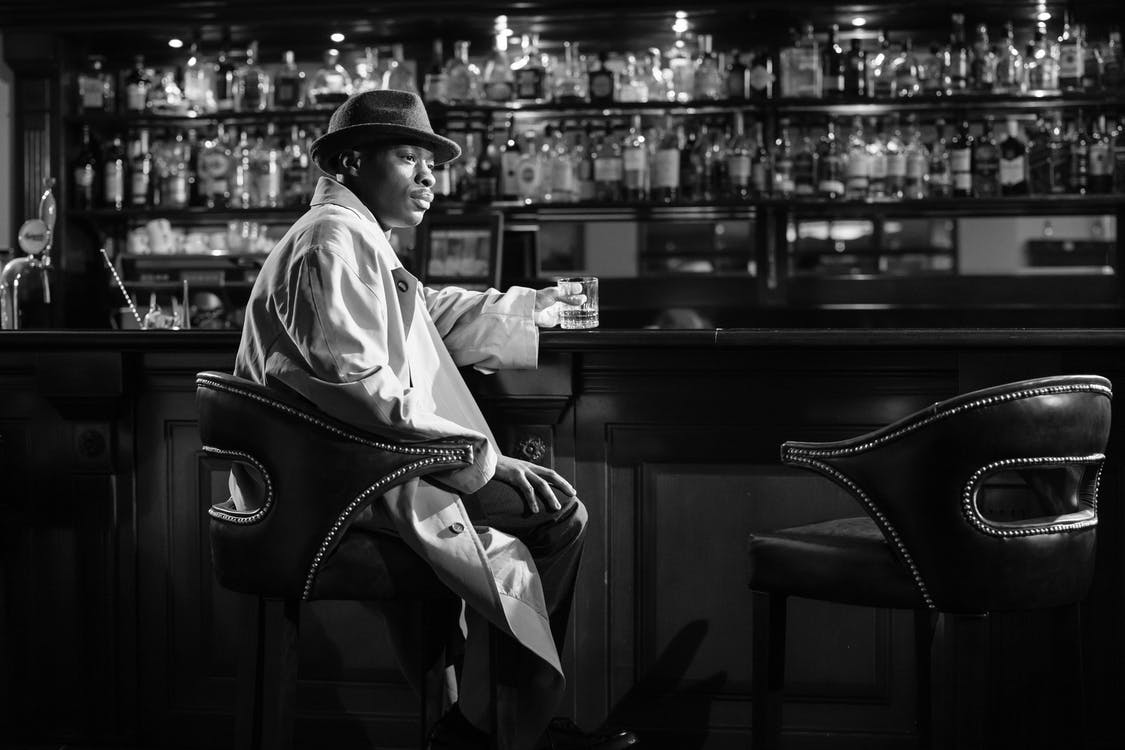 Monochrome Photo of Man Sitting in Front of  Bar Counter