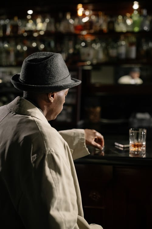 Photo of Man Sitting in Front of Bar Counter